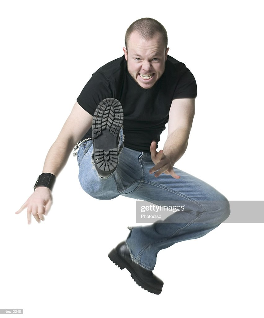 full body shot of a young adult male in a black shirt as he angrily jumps up and kicks : Foto de stock