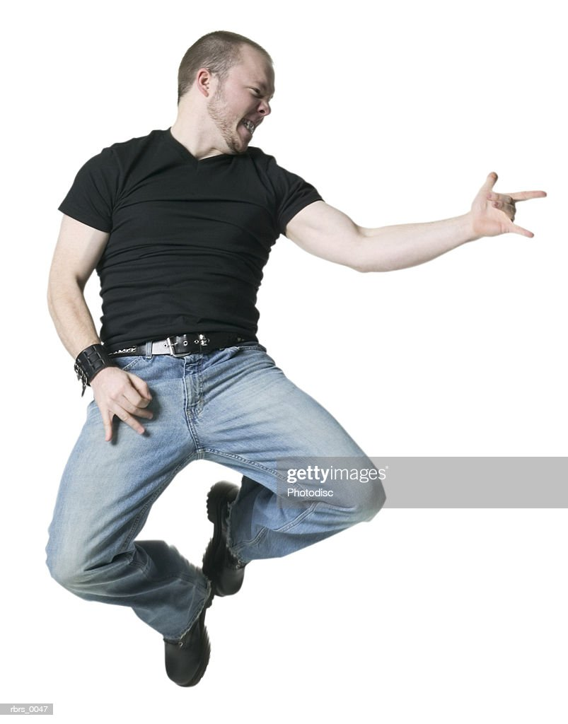 full body shot of a young adult male in a black shirt as he angrily jumps up and points : Foto de stock
