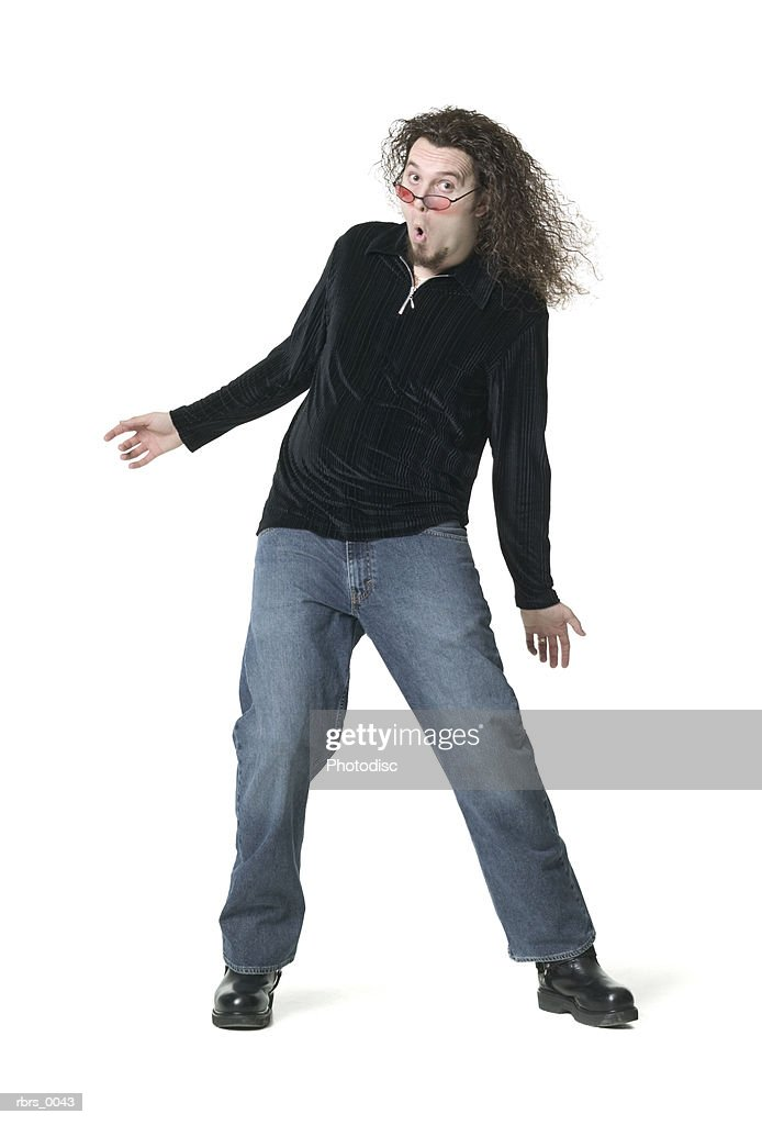 full body shot of a young adult male in a black shirt as he moves around playfully : Foto de stock