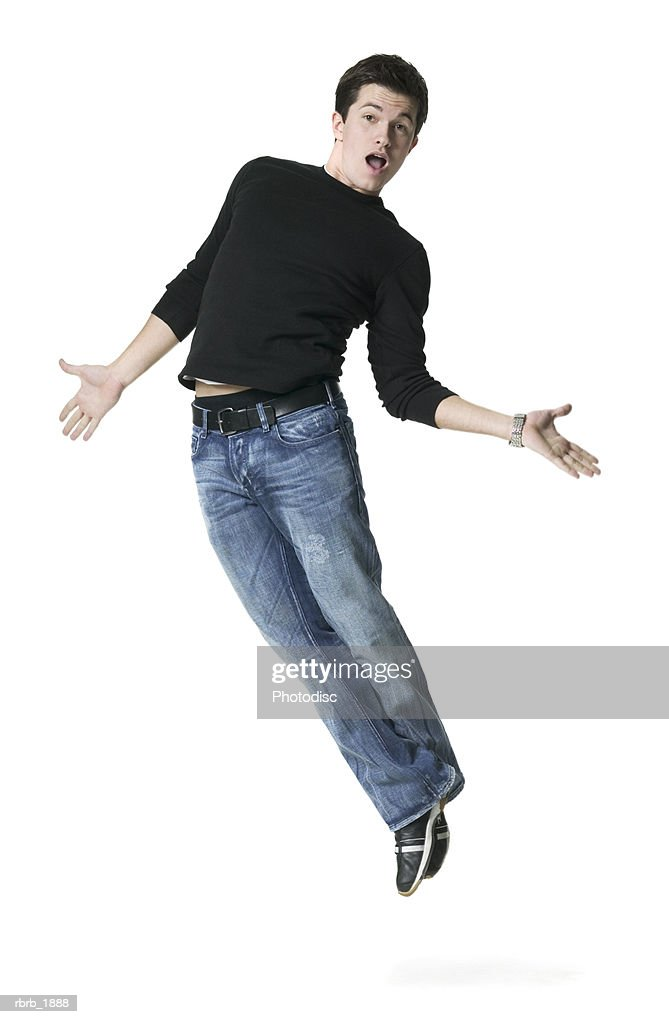 full body shot of a young adult male in a black shirt as he playfully jumps up : Stockfoto