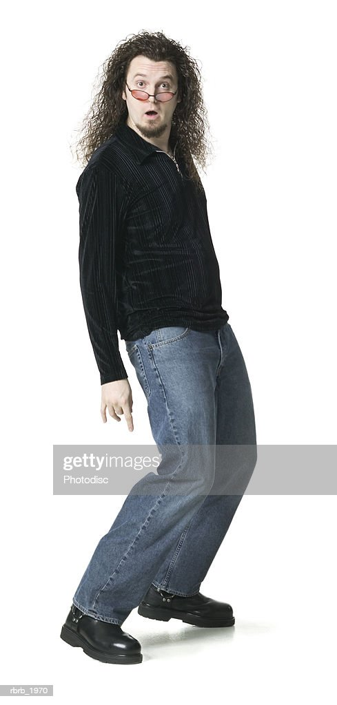 full body shot of a young adult male in a black sweater as he stikes a fun pose : Stockfoto