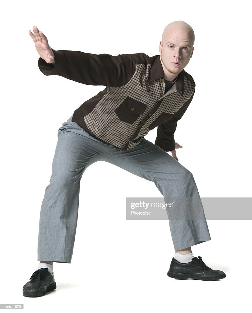 full body shot of a young adult male in a brown checkered shirt as he strikes a silly pose : Stockfoto