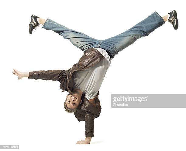 full body shot of a young adult male in a leather jacket as he does a flip - cartwheel stock pictures, royalty-free photos & images