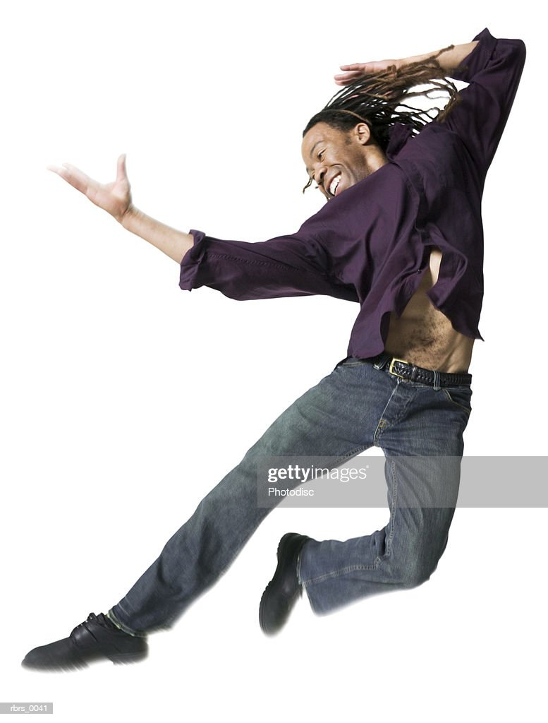 full body shot of a young adult male in a purple shirt as he jumps sideways through the air : Foto de stock