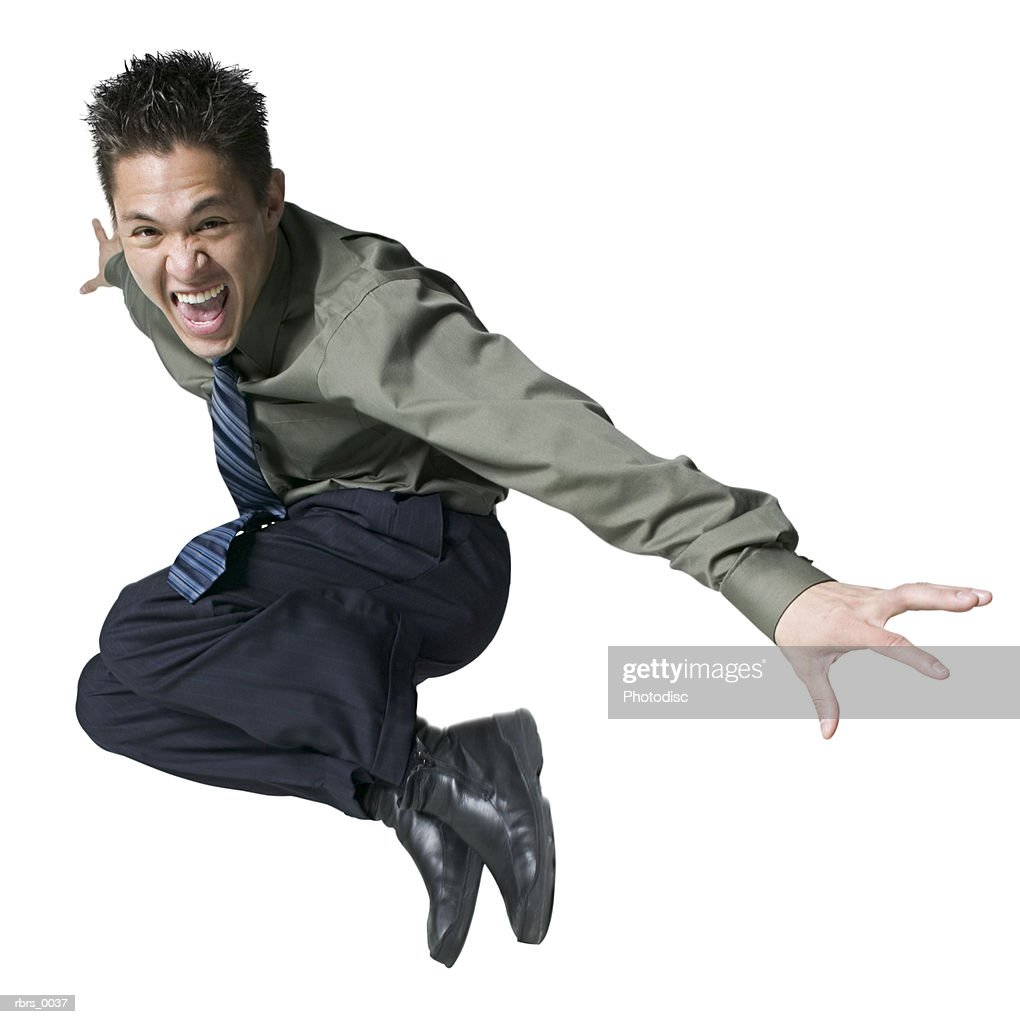 full body shot of a young adult male in a shirt and tie as he jumps up in the air : Foto de stock