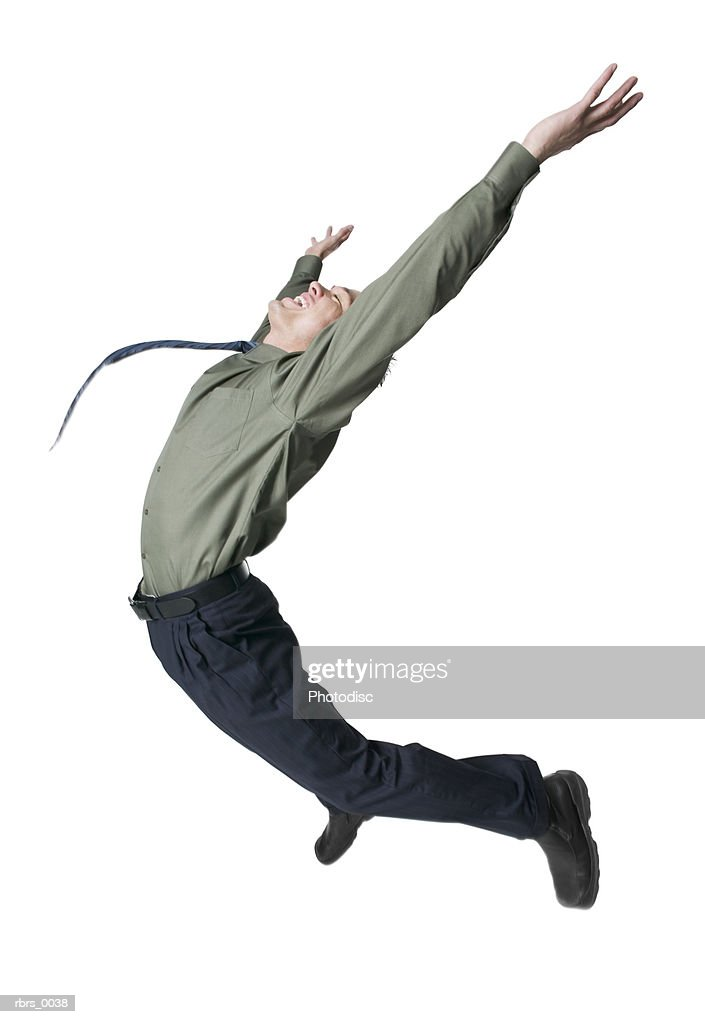full body shot of a young adult male in a shirt and tie as he jumps up playfully in the air : Foto de stock