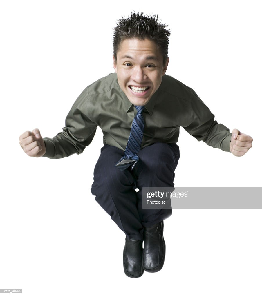 full body shot of a young adult male in a shirt and tie as he jumps up and smiles : Foto de stock