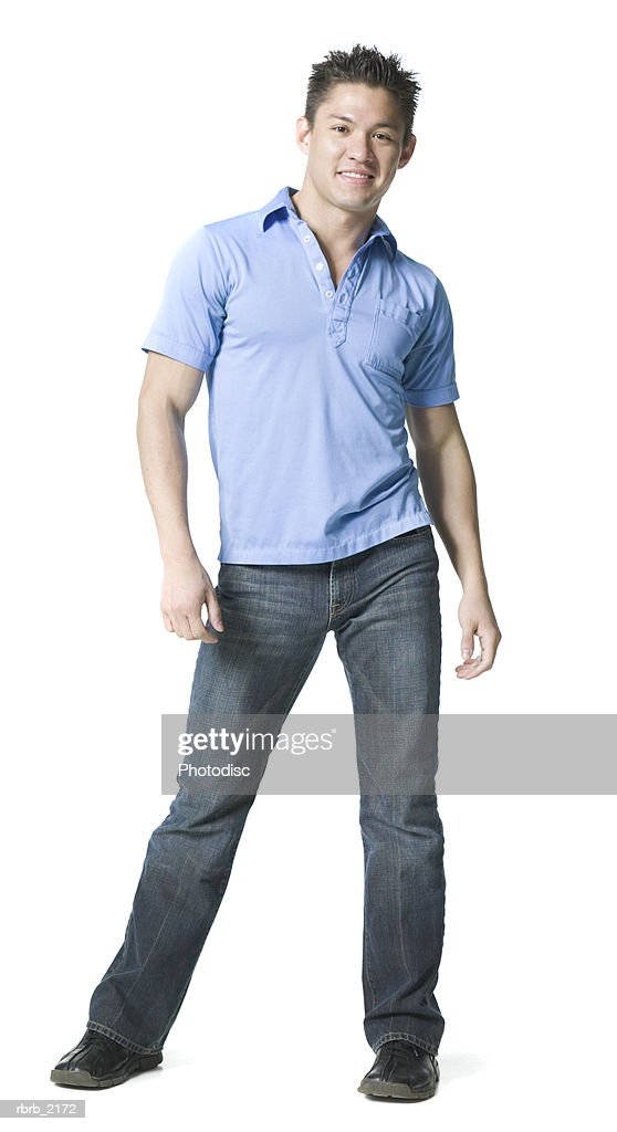 full body shot of a young adult male in jeans and a blue shirt as he smiles : Foto de stock
