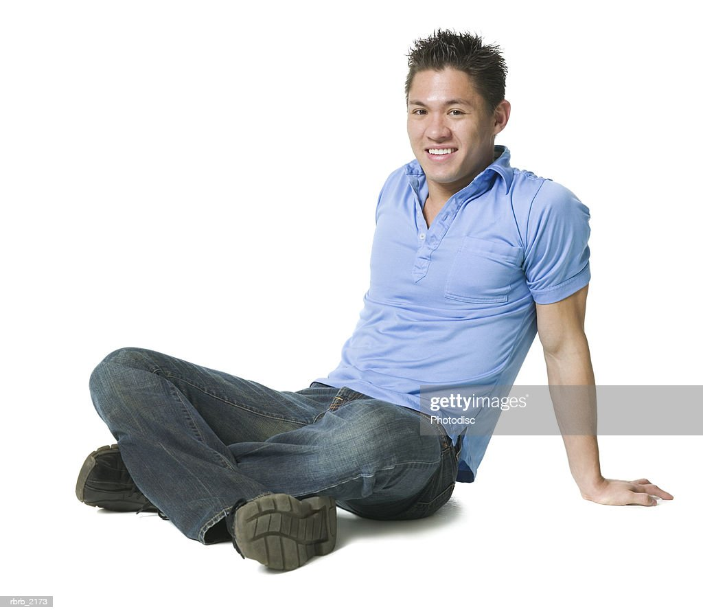 full body shot of a young adult male in jeans and a blue shirt as he sits down and smiles : Foto de stock