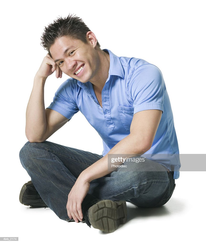 full body shot of a young adult male in jeans and a blue shirt as he sits and smiles : Stockfoto