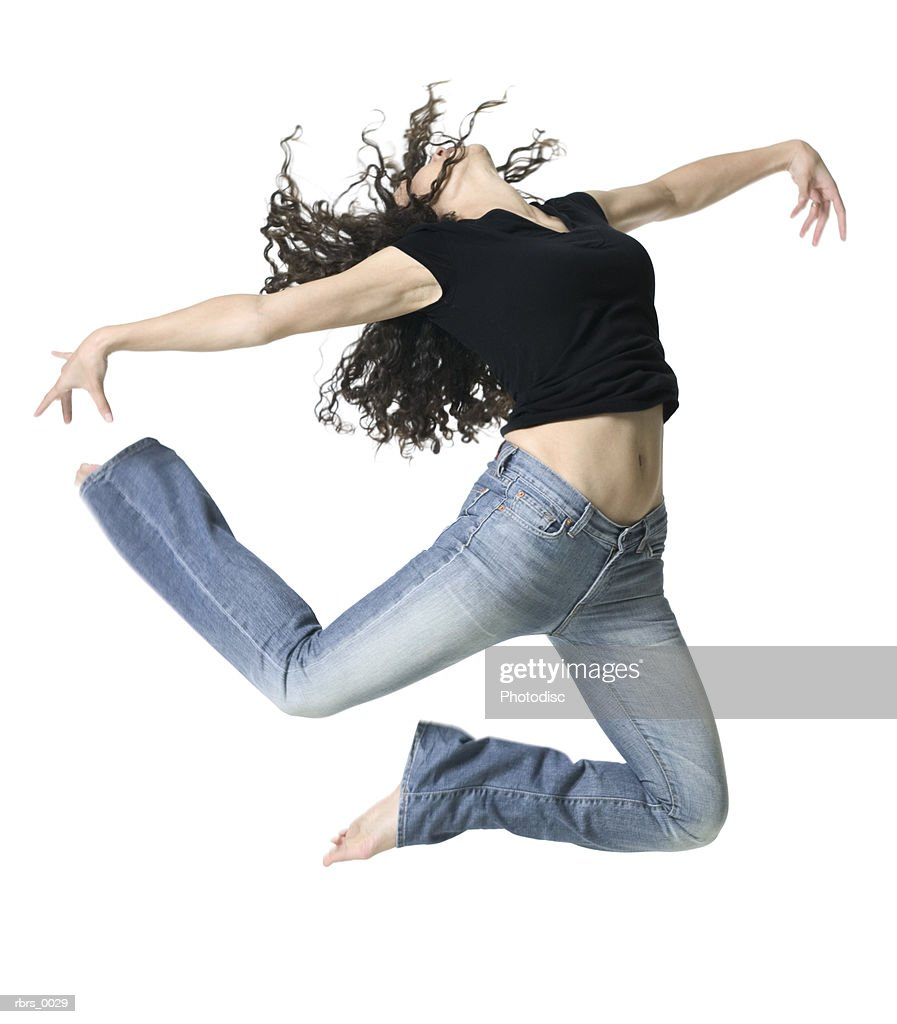 full body shot of a young adult woman as she energetically jumps up in the air : Stockfoto
