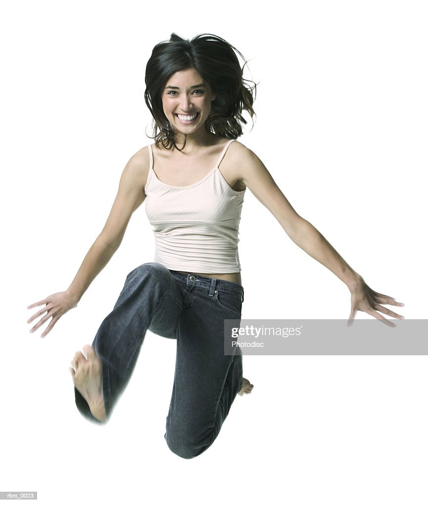 full body shot of a young adult woman as she jumps through the air and smiles : Foto de stock