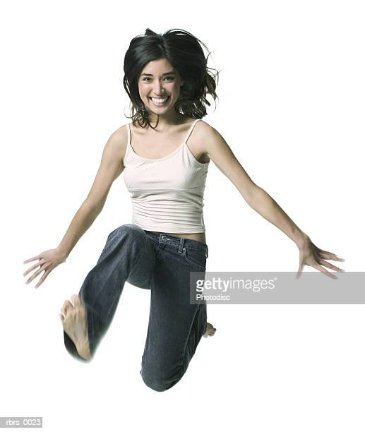 full body shot of a young adult woman as she jumps through the air and smiles