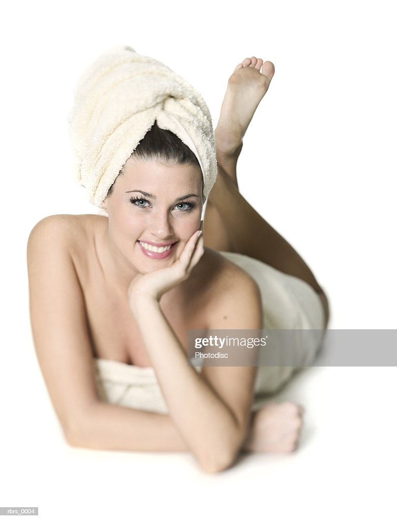 full body shot of a young adult woman as she lays down while wrapped in a towel : Stock Photo