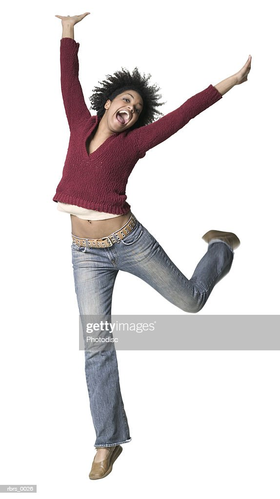 full body shot of a young adult woman as she playfully jumps and throws up her arms : Foto de stock