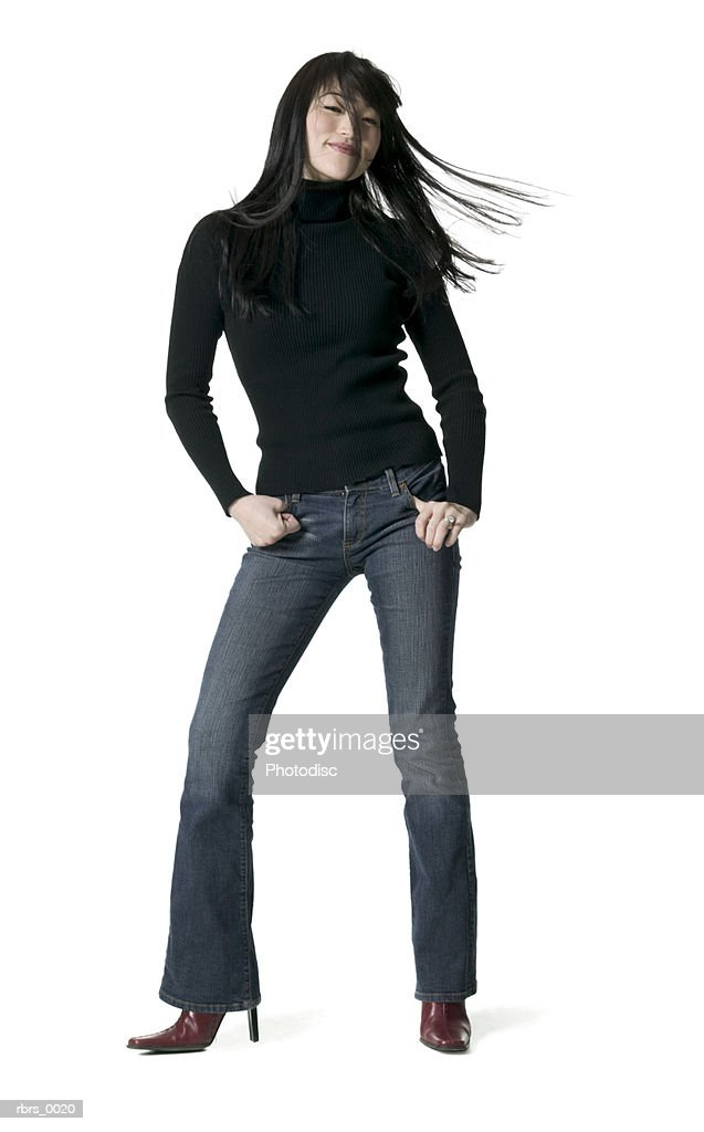 full body shot of a young adult woman as she playfully tosses her hair around : Foto de stock