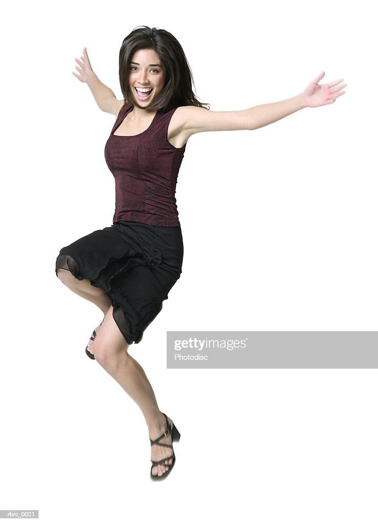 full body shot of a young adult woman as she skips and jumps around : Foto de stock