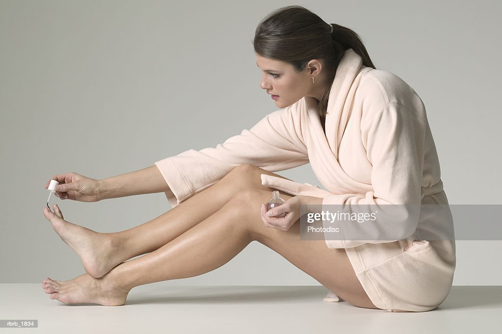full body shot of a young adult woman in a bathrobe as she paints her toenails : Stockfoto