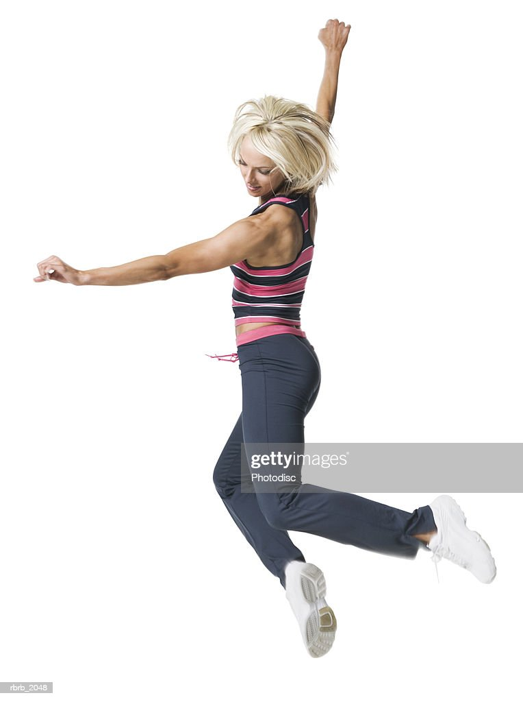 full body shot of a young adult woman in a colorful workout outfit as she jumps through the air : Stockfoto