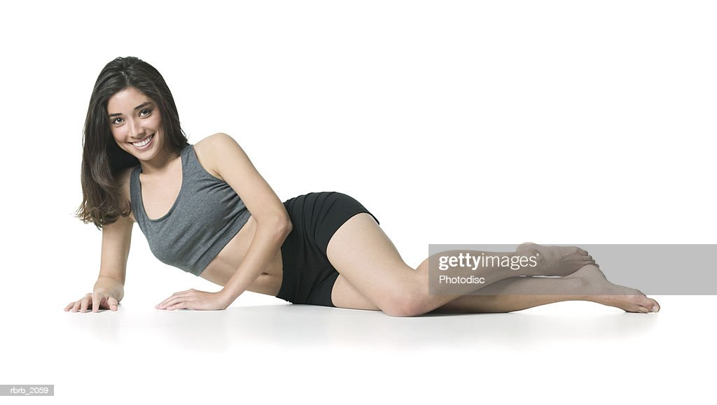 full body shot of a young adult woman in a grey and black workout outfit as she lays down on her side : Stockfoto