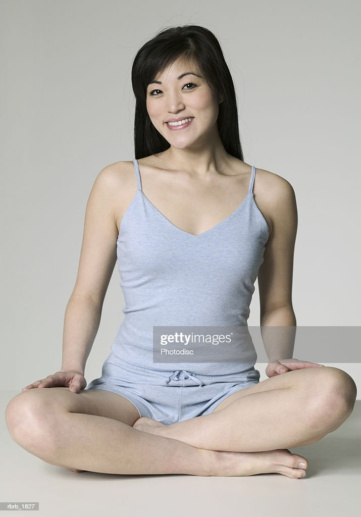 full body shot of a young adult woman in a grey tank top and shorts as she sits and smiles : Stockfoto