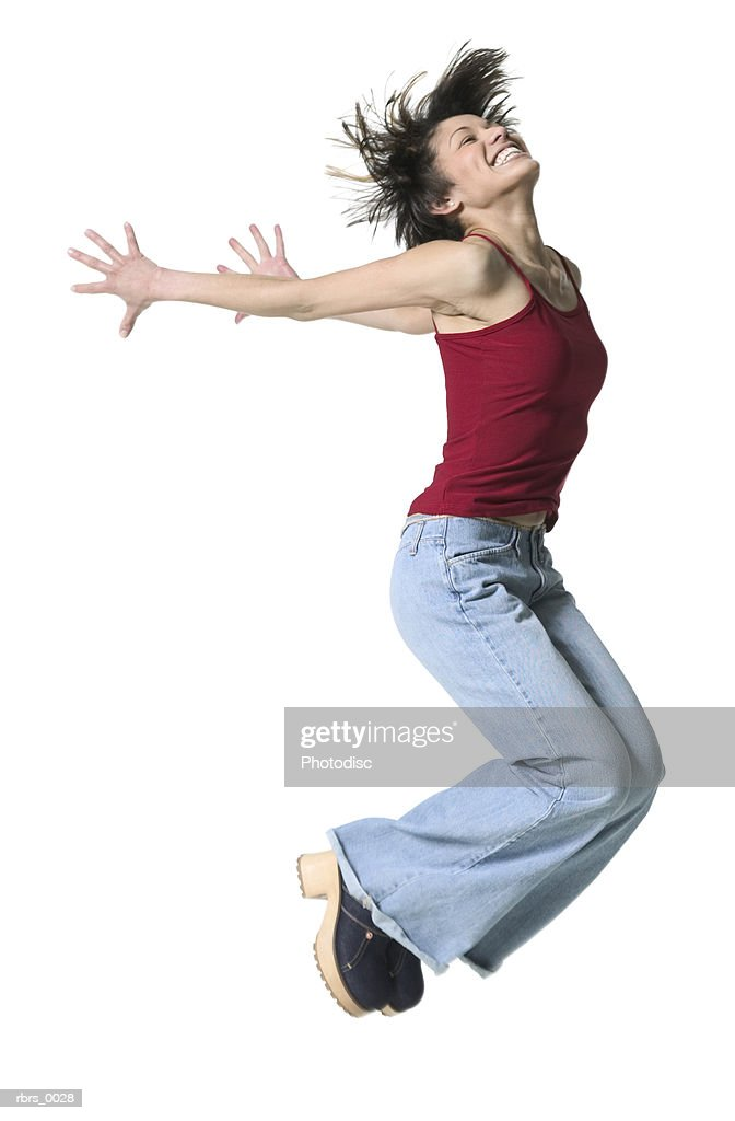 full body shot of a young adult woman in a red tank top as she jumps through the air : Foto de stock