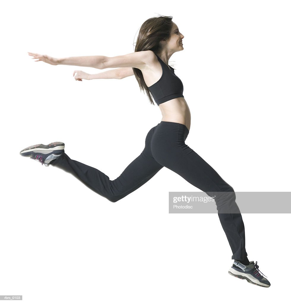 full body shot of a young adult woman in a workout outfit as she jumps through the air : Foto de stock