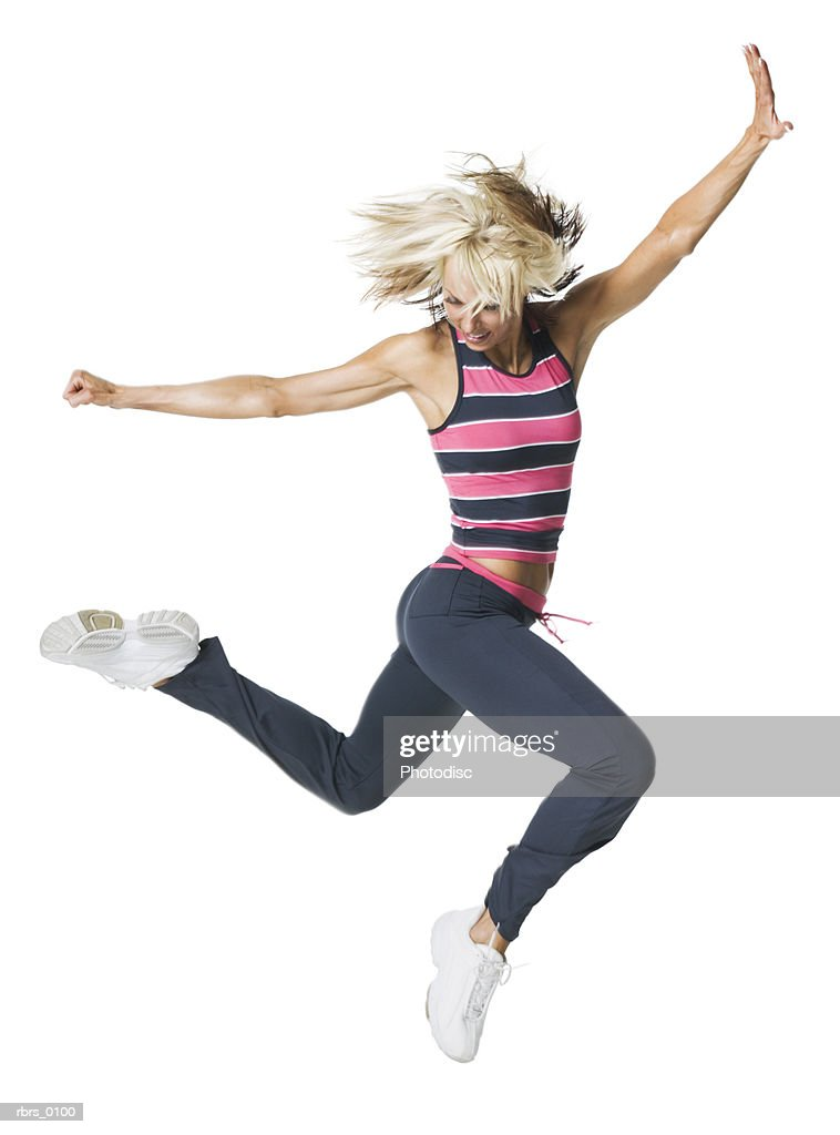 full body shot of a young adult woman in a workout outfit as she runs and jumps through the air : Foto de stock