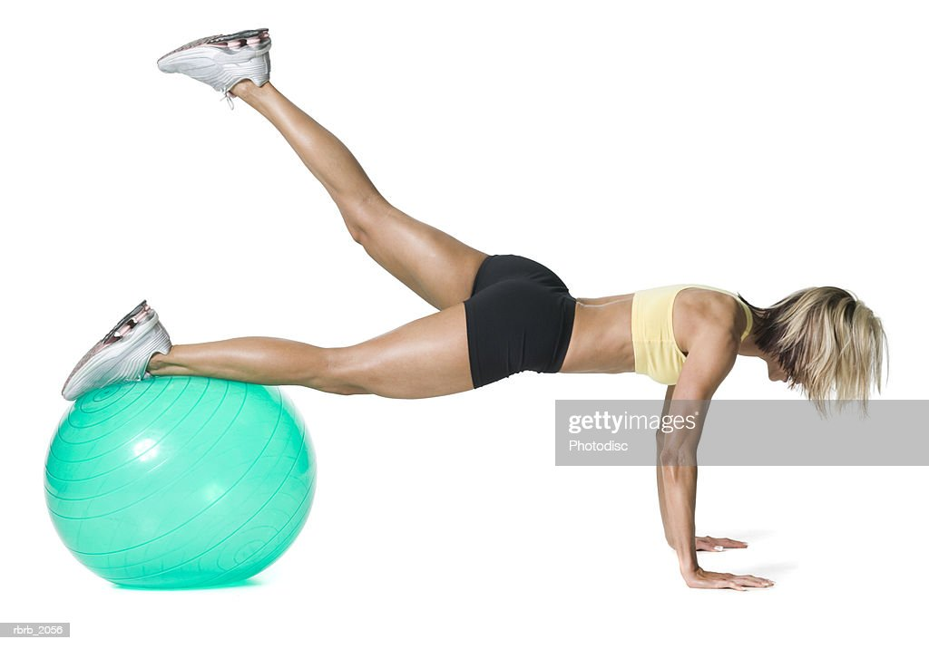 full body shot of a young adult woman in a yellow sports bra as she sretches her legs with a ball : Stockfoto
