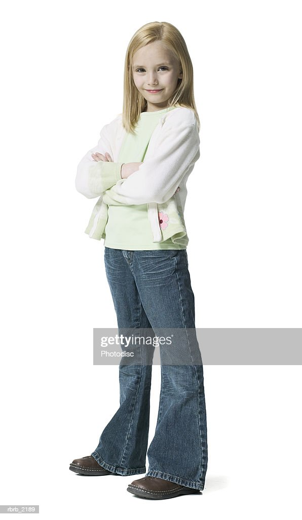 full body shot of a young female child as she folds her arms and smiles at the camera : Foto de stock