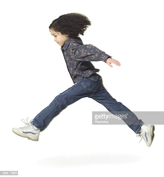 full body shot of a young female child in blue floral print shirt as she runs and jumps through the air