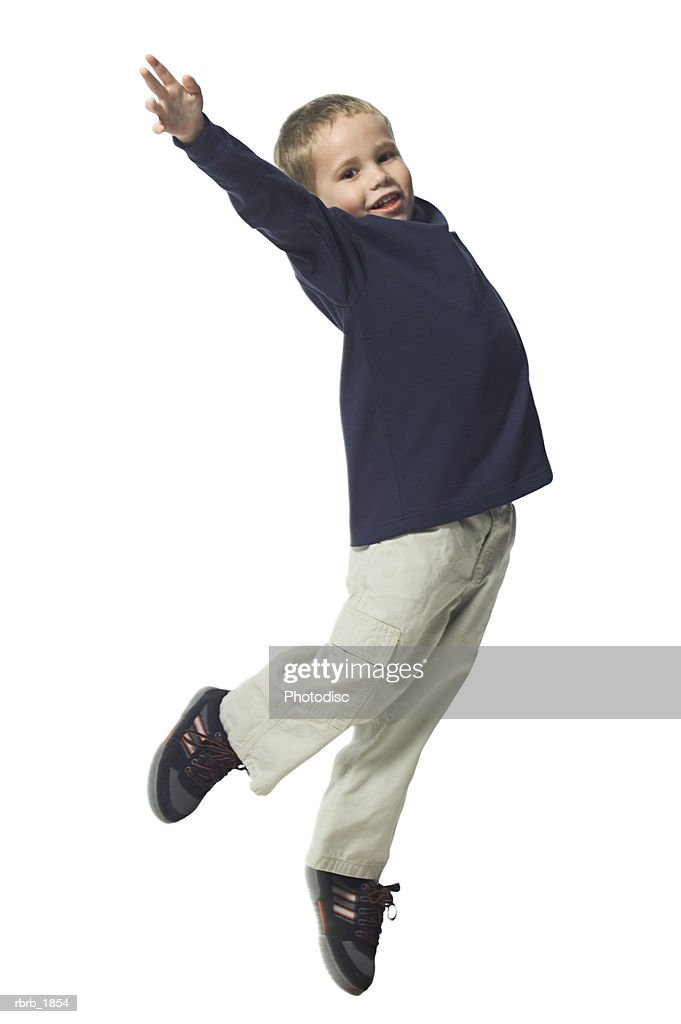 full body shot of a young male child in a blue shirt as he playfully jumps up into the air : Stockfoto