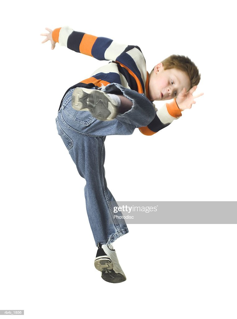 full body shot of a young male child in a striped shirt as he playfully jumps and kicks through the air : Stockfoto