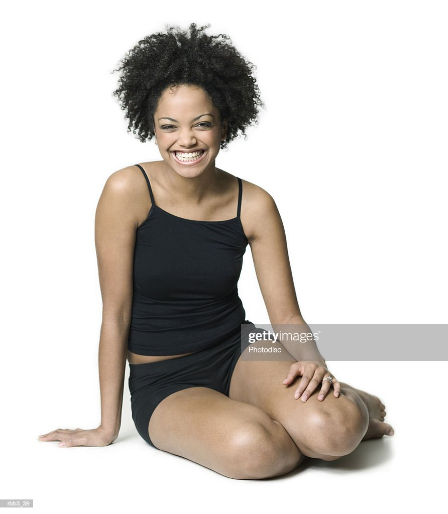 full body shot of a young woman in a black workout outfit as she smiles brightly : Stockfoto