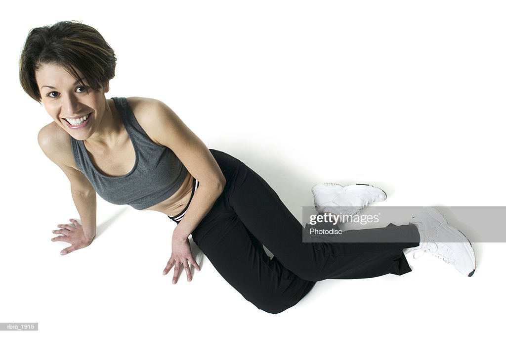 full body shot of an adult female in a workout outfit as she leans on her side and smiles up at the camera : Stockfoto