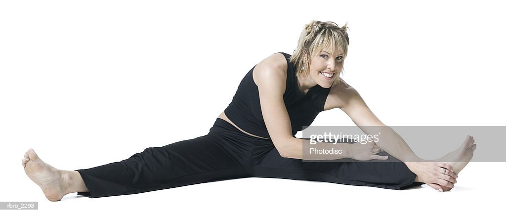 full body shot of an adult woman in a black workout outfit as she stretches out : Foto de stock