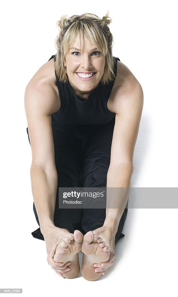 full body shot of an adult woman in a black workout outfit as she warms up and stretches out : Foto de stock