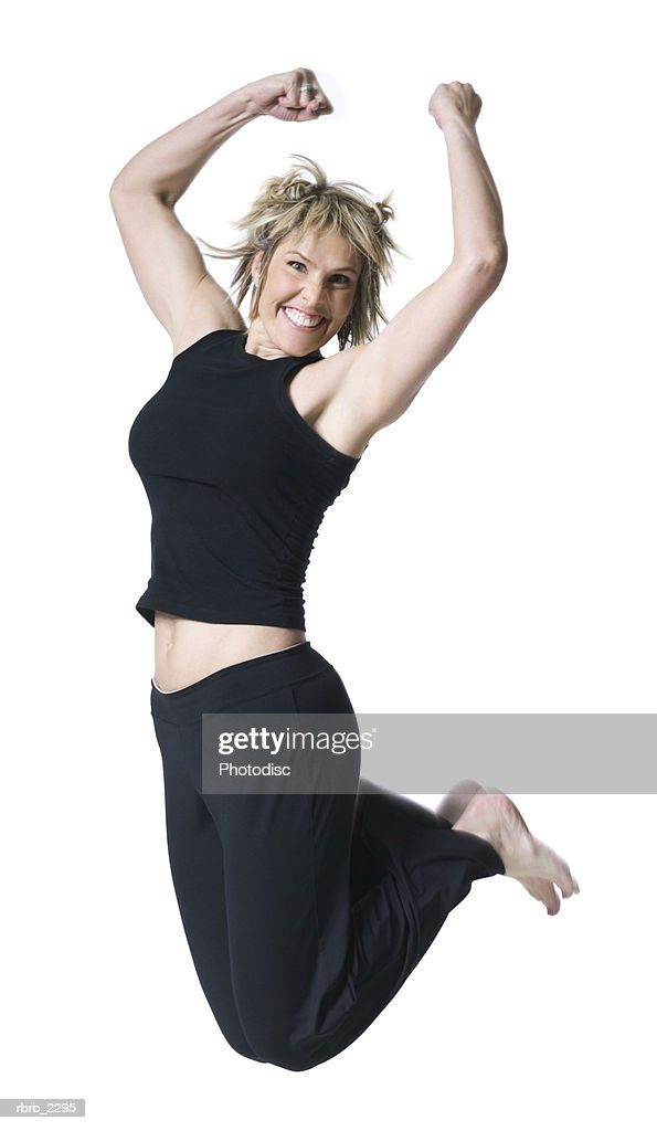 full body shot of an adult woman in a black workout outfit as she jumps up into the air : Foto de stock