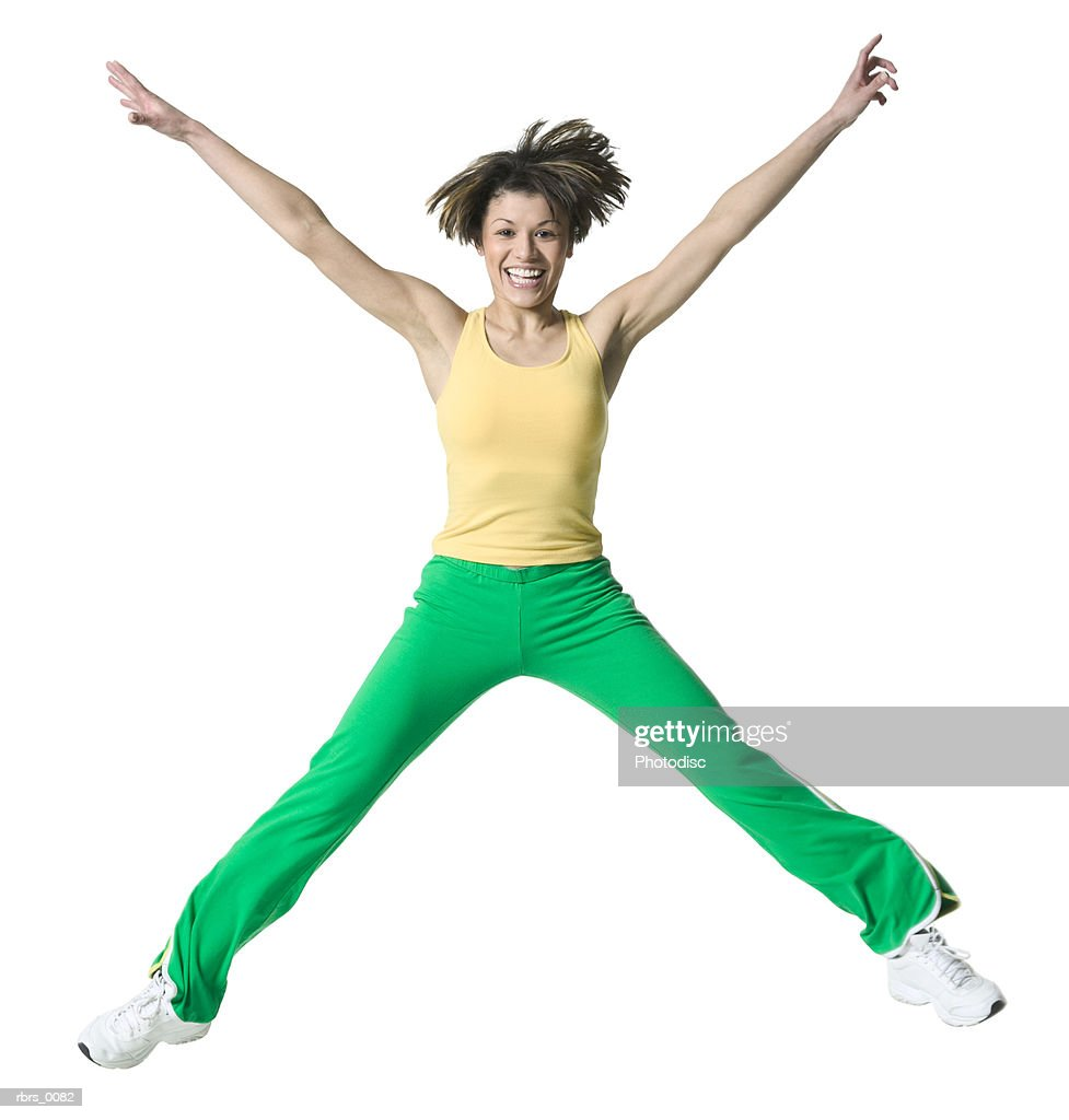 full body shot of an adult woman in a workout outfit as she jumps up into the air : Foto de stock