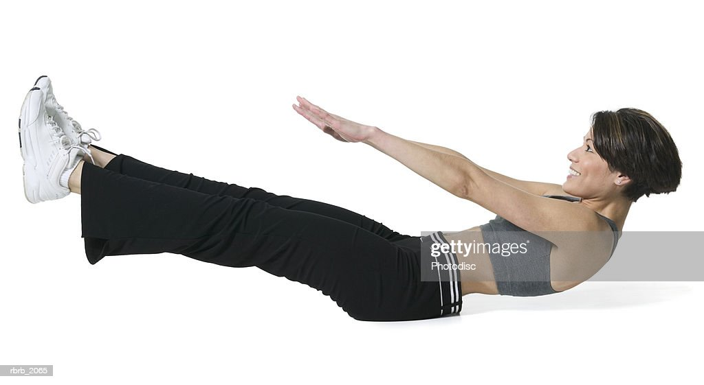 full body shot of an adult woman in a workout outfit as she lays down and stretches out : Stockfoto
