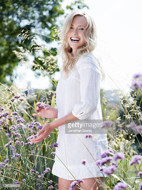 full body shot of female standing in wild flowers - beautiful people stock pictures, royalty-free photos & images