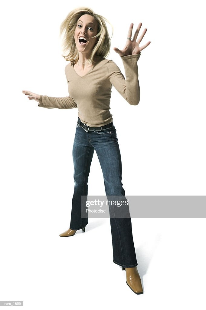 full body shot of young adult blonde female in a tan sweater as she playfully tosses around her arms : Stockfoto