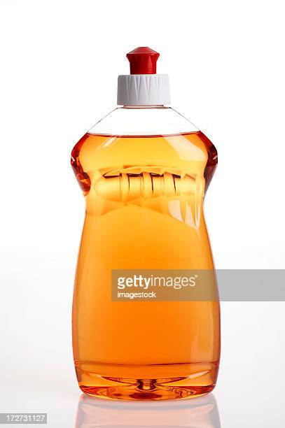 Full bottle of orange dishwashing liquid on white background