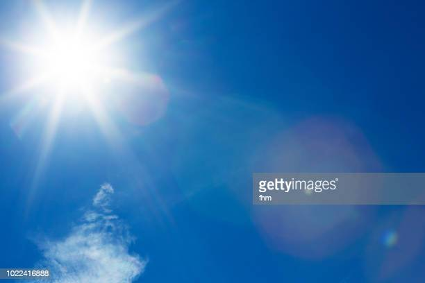 full bright sun in the sky - suns stock photos and pictures
