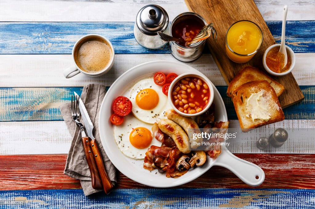 Full English breakfast in white pan with fried eggs, sausages, bacon, beans, toasts, orange fresh and coffee on wooden background : Stock Photo