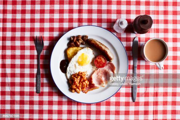 Full English breakfast on checked table cloth, overhead view