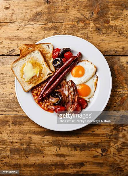 Full English Breakfast with fried eggs, sausages, bacon, beans, toasts, tomatoes and mushrooms on wo