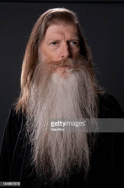 Full face of long bearded man in black robe-isolated