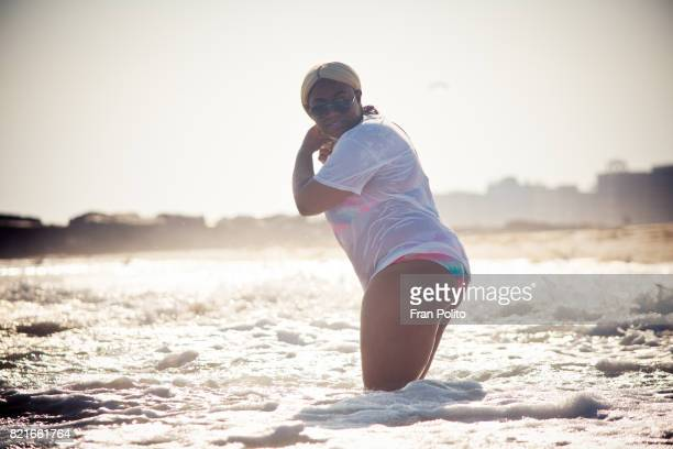 A full figure young black woman at the beach.