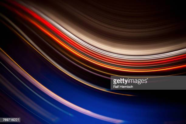 full frame abstract image of colorful light trails against black background - striped stock photos and pictures
